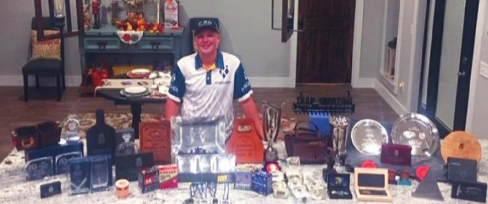 Dakota Sliger poses with his array of trophies he has won during his Trapshooting tournaments. He was recenting named on the All-American Team. Courtesy photo