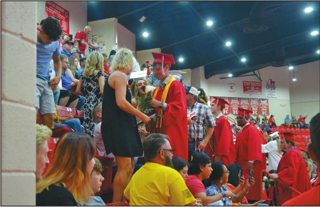 A Kingston graduate gives a white rose to his mom at the KHS Commencement on June 5. Matt Caban • The Madill Record