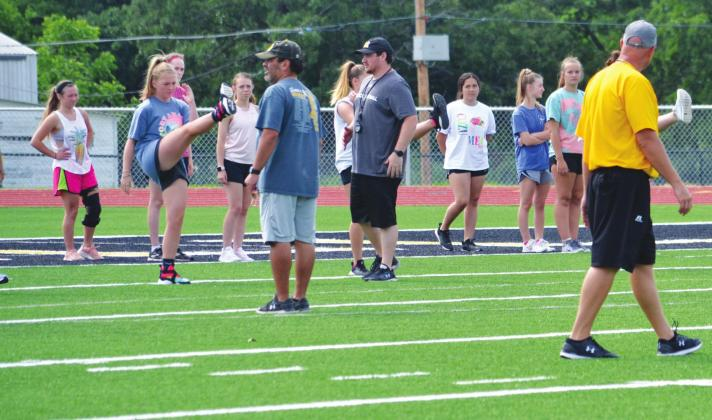 New Madill strength and condtioning coach Alex Rainwater (center with whistle) leads athletes in a stretching drill on the first day of Madll Summer Pride June 1 at Blake Smiley Field as fellow coaches Jose Cortes (center left) and Chad Speer (right) look on. Matt Caban • The Madill Record