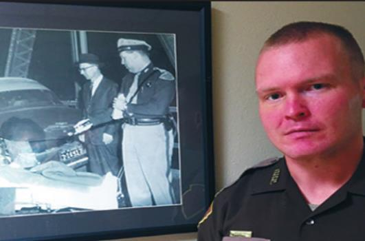 Garrett Schulze stands by a photo of his grandfather as a trooper. Courtesy photo